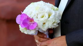 Beautiful wedding bouquet of white roses and pink orchids  for bride in hands of bridegroom stock video footage