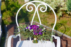 Beautiful wedding bouquet on a white wrought-iron chair. Stock Image