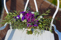 Beautiful wedding bouquet on a white wrought-iron chair. Royalty Free Stock Images