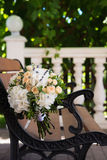 Beautiful wedding bouquet on a wooden bench. Beautiful wedding bouquet of roses and hydrangeas lying on a wooden bench Royalty Free Stock Image