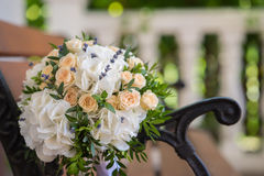 Beautiful wedding bouquet on a wooden bench. Beautiful wedding bouquet of roses and hydrangeas lying on a wooden bench Royalty Free Stock Photography