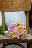 Beautiful wedding bouquet on a wooden shabby chair.  Royalty Free Stock Images