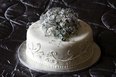 Beautiful Wedding Cake. Silver and white wedding cake adorned with diamonds and frosted flowers Stock Photos