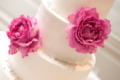 Beautiful wedding cake. Beautiful close up of a white wedding cake decorated with peonies and pearls Royalty Free Stock Images