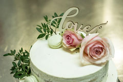 Beautiful wedding cake with cream With text Love on top pink flowers roses Stock Images