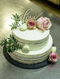 Beautiful wedding cake with cream With text Love on top pink flowers roses Royalty Free Stock Images