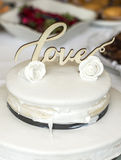 Beautiful wedding cake with cream With text Love on top white flowers roses Stock Image