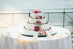 A beautiful wedding cake in four levels is on the table against the background of the picturesque lake