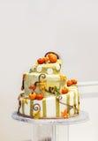 Beautiful wedding cake in orange and creme, with pumpkin Stock Photos