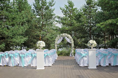 Beautiful wedding ceremony decorated with arch, flowers and chairs. Beautiful wedding ceremony design decoration elements with arch, floral design, flowers and Stock Photo