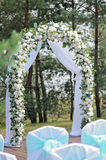 Beautiful wedding ceremony decorated with arch, flowers and chairs. Beautiful wedding ceremony design decoration elements with arch, floral design, flowers and Stock Photos