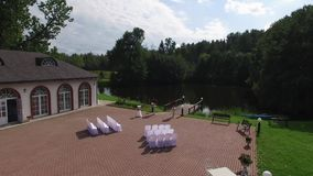 Beautiful wedding ceremony decoration. Aerail drone shot in park with pond and palace building, country side. stock video footage