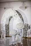 Beautiful wedding ceremony design decoration elements with arch, floral , flowers, chairs indoor. Beautiful wedding ceremony design decoration elements with arch Royalty Free Stock Photography