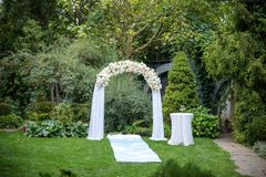 Beautiful wedding ceremony outdoors. Decorated chairs stand on the grass. Wedding arch made of cloth and white and pink flowers on stock photos