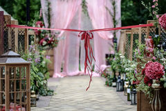 Beautiful wedding ceremony outdoors. Decorated chairs and wedding aisle with an awesome bow.. Rustic style. Royalty Free Stock Image