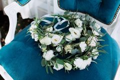 Beautiful wedding circlet lies on vintage blue beige chair. Bouquet consists of white roses, eucalyptus and eustoma Royalty Free Stock Image