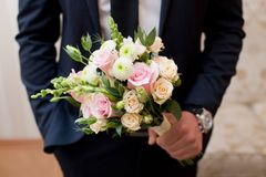 Beautiful wedding colorful nosegay in grooms hands. Beautiful wedding colorful nosegay of pink and peach roses royalty free stock photography