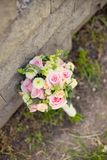 Beautiful wedding colorful nosegay near the stone. Beautiful wedding colorful nosegay of pink and peach roses stock photo