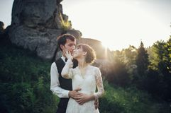 Romantic newlywed couple posing in sunset lights on majestic roc. Beautiful wedding couple bride and groom at wedding day outdoors on the mountains rock on sea Royalty Free Stock Photography