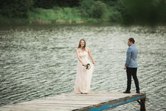 Beautiful wedding couple, bride,groom kissing and posing on the bridge near lake Royalty Free Stock Image