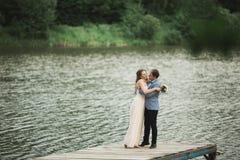 Beautiful wedding couple, bride,groom kissing and posing on the bridge near lake Stock Photos
