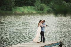 Beautiful wedding couple, bride,groom kissing and posing on the bridge near lake Stock Image