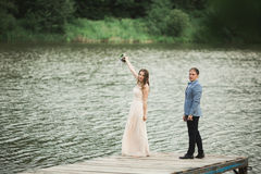 Beautiful wedding couple, bride,groom kissing and posing on the bridge near lake Stock Images