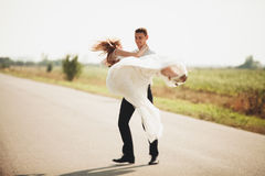 Beautiful wedding couple, bride and groom posing on road Stock Images