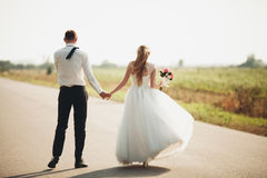 Beautiful wedding couple, bride and groom posing on road Royalty Free Stock Photos