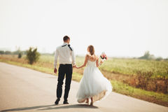 Beautiful wedding couple, bride and groom posing on road Royalty Free Stock Photography
