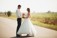 Beautiful wedding couple, bride and groom posing on road Stock Photography