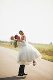 Beautiful wedding couple, bride and groom posing on road Royalty Free Stock Photo