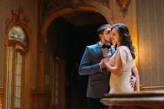 Beautiful wedding couple embracing and kissing near balustrade at gorgeous antique stairs with the background of royal Stock Photo