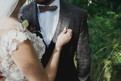 Beautiful wedding couple in the forest. The bride touches the groom in bow tie tenderly. Wedding buttonhole and checkered suit in stock photo