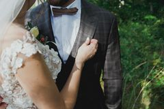 Beautiful wedding couple in the forest. The bride touches the groom in bow tie tenderly. Wedding buttonhole and checkered suit in stock image
