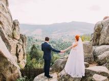 Beautiful wedding couple holding hands at wonderful rocky landscape of Carpathians mountains. Stock Photo