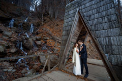 Beautiful wedding couple hugs on the wooden bridge in mountains. Waterfall background Royalty Free Stock Images