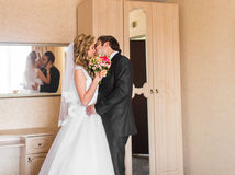 Beautiful wedding couple indoors. They kiss and hug each other Royalty Free Stock Images