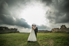 Beautiful wedding couple kissing. On the background of the ruined castle and cloudy sky Royalty Free Stock Images