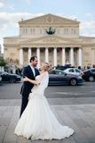 Beautiful wedding couple in Moscow, the bride and groom in a white dress in the street on the background of the Bolshoi Royalty Free Stock Image