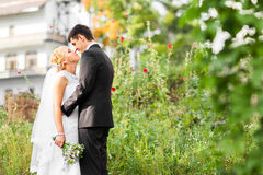 Beautiful wedding couple outdoors. They kiss and hug each other Royalty Free Stock Images