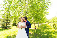 Beautiful wedding couple in park. They kiss and hug each other Stock Image