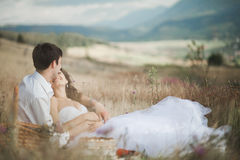 Beautiful wedding couple at picnic with fruit and cake on a background of mountains Royalty Free Stock Images