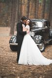 Beautiful wedding couple posing near splendid retro car Stock Photos
