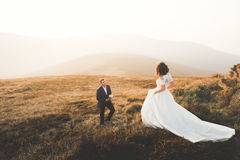 Beautiful wedding couple posing on top of a mountain at sunset.  Stock Image