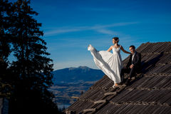 Beautiful wedding couple posing on the top of  roof. Amazing mountain landscape background Stock Photography