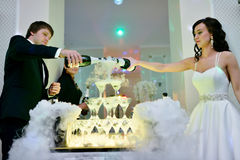 Beautiful wedding couple is pouring champagne indoors Royalty Free Stock Photos