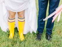 Feet of the bride and groom walk in rainy weather. Beautiful Wedding couple in the rain, walk under the rain Stock Photography