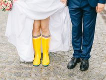 Feet of the bride and groom walk in rainy weather. Beautiful Wedding couple in the rain, walk under the rain Royalty Free Stock Photography