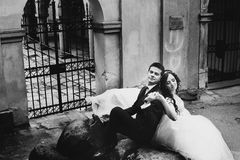 Beautiful wedding couple rests on the big stone in a backyard Royalty Free Stock Photography